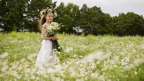 白色礼服的逗人喜爱的青少年的在花草甸的女孩有在头的花圈的和花束 影视素材