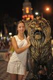 白色礼服的青少年的女孩在狮子的雕塑旁边 免版税库存照片