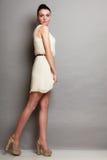 白色礼服的魅力女孩在灰色 库存图片