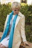 白色礼服的,外套,蓝色围巾坐妇女金发碧眼的女人室外 时装模特儿射击 图库摄影