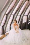 白色礼服的年轻美丽的坐在窗口附近的新娘和面纱拿着花束 库存照片