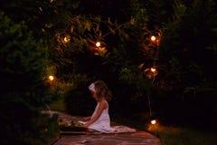 白色礼服阅读书的可爱的儿童女孩在夏天用光装饰的晚上庭院里 免版税库存照片