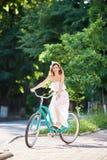 白色礼服骑马葡萄酒蓝色自行车的美丽的妇女在公园 免版税库存图片
