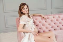 白色礼服peignoir的快乐的怀孕的年轻女人坐桃红色沙发,显示她的赤裸腹部,看照相机 库存图片