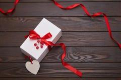 白色礼物盒包裹与在木背景的红色丝带 免版税库存照片
