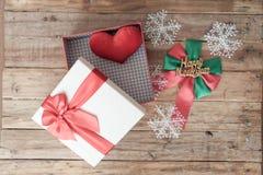 白色礼物盒和红色丝带和微型心脏里面在木头后面 免版税库存照片