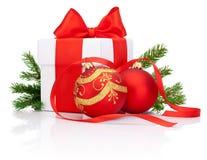 白色礼物盒栓与红色丝带、装饰圣诞节球和被隔绝的杉树分支 免版税库存照片