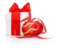 白色礼物盒栓与红色丝带和两被隔绝的圣诞节球 库存图片