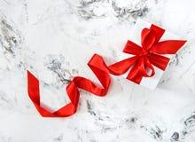 白色礼物盒红色丝带弓明亮的大理石背景 免版税库存图片