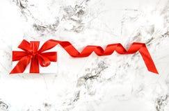 白色礼物盒红色缎丝带弓大理石背景 库存照片