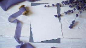 白色空插件、信封和丝带在桃红色和蓝色织品背景与淡紫色花在白色 股票视频