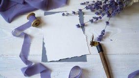 白色空插件、信封和丝带在桃红色和蓝色织品背景与淡紫色花在白色 影视素材