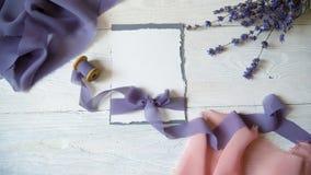 白色空插件、信封和丝带在桃红色和蓝色织品背景与淡紫色花在白色 股票录像