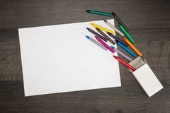 白色空白的纸片与五颜六色的蜡笔的 免版税库存照片