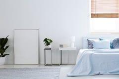 白色空的海报大模型在简单的旅馆卧室内部wi的 库存照片