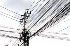 白色空间隔绝了缠结导线背景在路,在泰国电能的导线的在走的街道旁边天空背景 库存照片