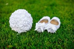 白色穿上鞋子新娘在草的婚礼花束 库存照片