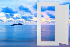 白色窗口空腹架沟有日落海滩背景 免版税库存图片