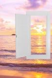 白色窗口空腹架沟有日落海滩背景 库存图片