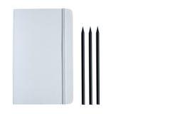 白色笔记本和三支黑铅笔 库存照片