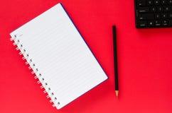 白色笔记本和黑铅笔和黑键盘在红颜色 免版税库存照片