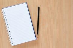 白色笔记本和黑铅笔在山毛榉上色背景与 免版税图库摄影