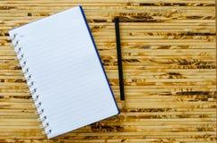 白色笔记本和黑铅笔在竹颜色背景与 免版税图库摄影