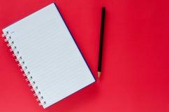 白色笔记本和黑铅笔在红颜色背景与co 库存图片