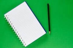 白色笔记本和黑铅笔在绿色背景与 免版税图库摄影