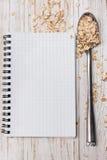 白色笔记薄和匙子用燕麦在木背景剥落 免版税库存图片