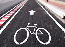 白色箭头和bycicle在车道路签字 免版税库存图片