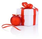 白色箱子栓与一个红色缎丝带弓和圣诞节球 免版税图库摄影