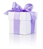 白色箱子附加查出的紫色缎丝带弓 免版税图库摄影