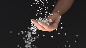 白色粒子落入手 免版税图库摄影