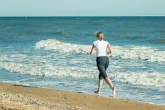 白色粗呢夹克的一名妇女在海滩跑步 免版税库存照片