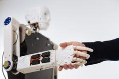 白色精心制作的机器人与人握手 免版税库存图片