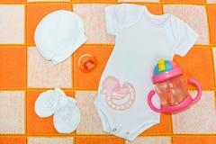 白色紧身衣裤、连裤外衣、白色盖帽、白色赃物、安慰者和teether 婴孩的事在控制中毯子 免版税库存图片