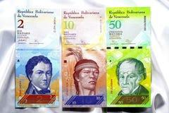 白色缎背景的委内瑞拉的钞票 库存照片