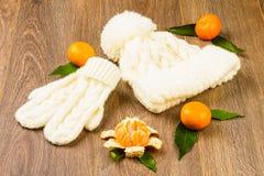 白色编织的盖帽、手套和蜜桔 库存照片