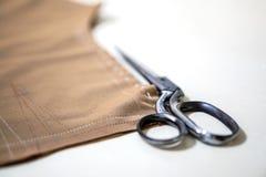 白色缝合的剪刀和织品纺织品做的布料 免版税图库摄影