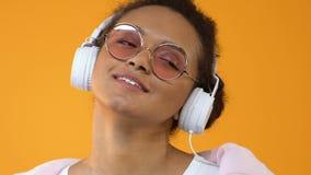 白色耳机的俏丽的年轻女人享受在黄色背景的音乐声音 股票视频