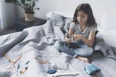 白色耳机的黑发女孩听到在一个灰色智能手机的音乐坐床 库存照片