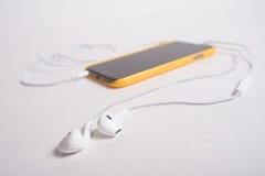白色耳机连接了到在黄色盒的黑电话 免版税图库摄影