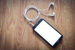 白色耳机附加智能手机 免版税库存照片