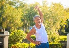 白色背心的灰色有胡子的老人在公园弯曲身体 图库摄影