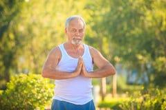 白色背心的灰色有胡子的老人在公园显示瑜伽 免版税库存图片