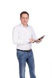 白色背景的成功的年轻学生在一件白色衬衣和蓝色牛仔裤在他的手上拿着片剂设备 免版税图库摄影