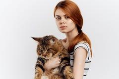 白色背景的美丽的妇女拿着一只猫,画象,宠物 免版税库存照片