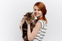 白色背景的美丽的少妇拿着一只猫 库存照片