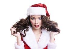 白色背景的美丽的愉快的年轻圣诞老人女孩 免版税库存图片